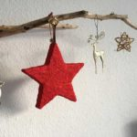 Treibholz-Ast als Advents-Deko an dem verschiedene Baum-Anhänger hängen