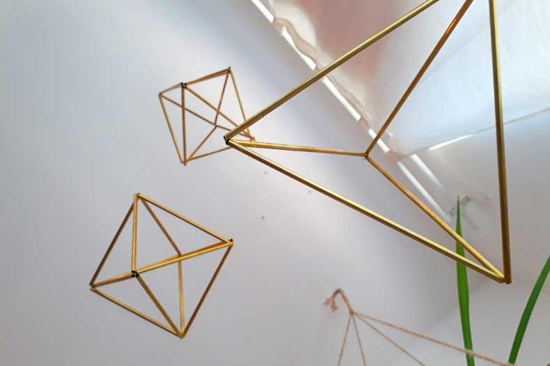 drei aufgehangene geometrische Formen aus Messing